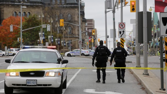 OTTAWA, CANADA - OCTOBER 22:  Ottawa police officers walk up Wellington St. near the National War Memorial where a soldier was shot earlier in the day, just blocks away from Parliament Hill, on October 22, 2014 in Ottawa, Canada. Officials are investigating multiple reports of shootings and suspects after at least one gunman shot a Canadian soldier and then entered Canada