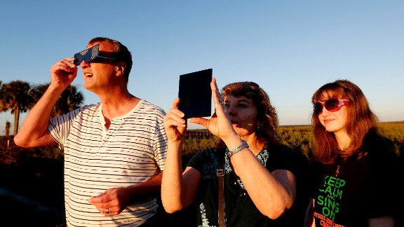 Andy, Cathy and Jessica Howell look at a partial eclipse of the sun on Thursday, October 23, in Gainesville, Florida. The solar eclipse was visible for most North Americans. Click through for more views: