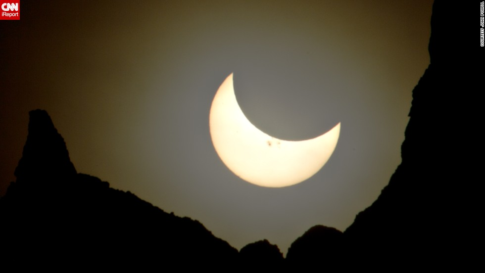 "<a href=""http://ireport.cnn.com/docs/DOC-1182579"">John Powell</a> photographed the eclipsed sun, which looked more like a crescent moon, hanging over Badlands National Park in South Dakota."