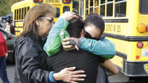 People embracein fron of school busses as they are reunited.