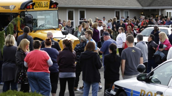 Parents crowd around busses as students arrive at the church.