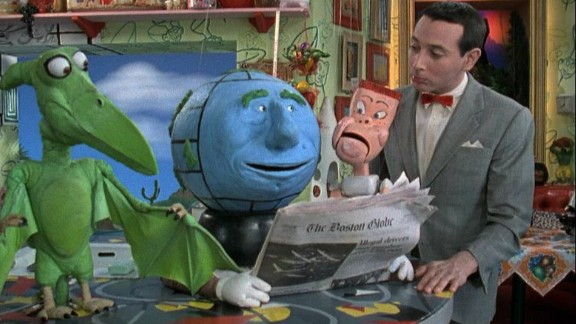 Globey the globe reads The Boston Globe as Pterri the pterodactyl, Randy the marionette puppet and Pee-wee look on.