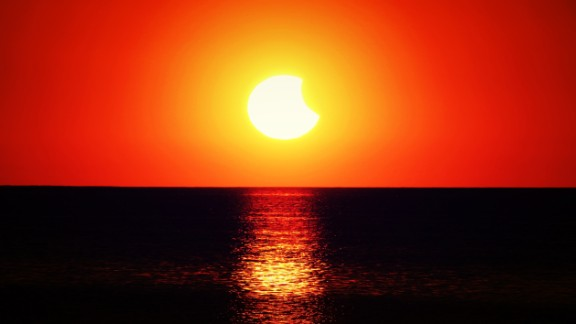 The solar eclipse illuminates the ocean in New Port Richey, Florida.