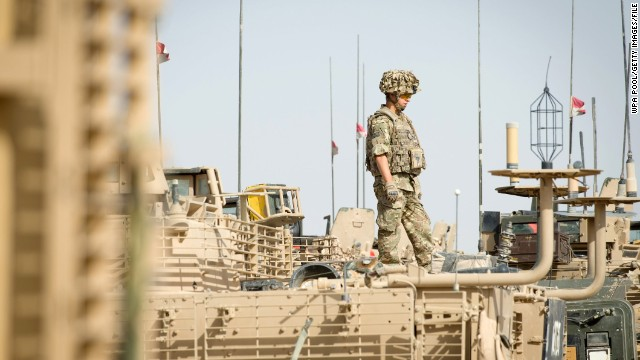 A British soldier stands on top of an armoured vehicle as UK PM David Cameron visits Camp Bastion on June 29, 2013.