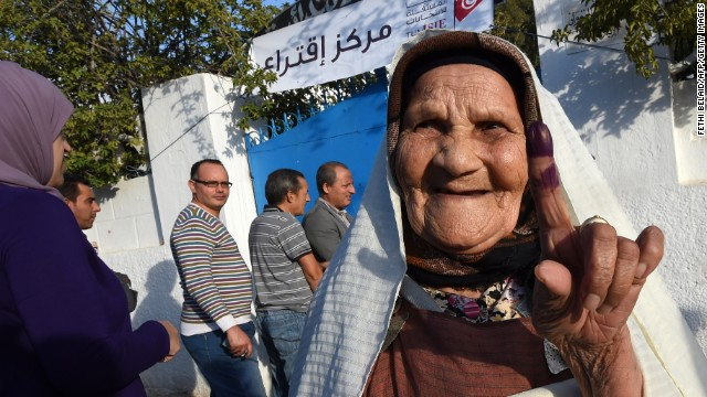 A Tunisian woman shows her ink-stained finger as she leaves Kairouan primary school turned into a polling station after voting in the country's election on October 26, 2014.