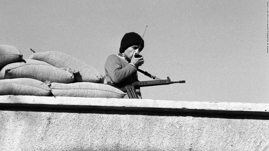 One of the kidnappers stands guard on the roof of the U.S. Embassy in Tehran on November 30, 1979.