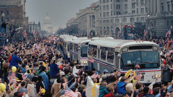 A caravan of buses carrying the former hostages and their relatives makes its way through the cheering crowd on Washington