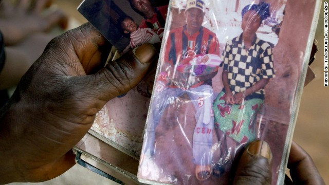 Family father Etienne Ouamouno holds a picture of his second wife Sia Dembadouno and their son Emile in his hands as he sits in front of their family house in the village of Meliandou, Guinea, 16 October 2014. 31-year old Etienne is the father one-year old Emile Ouamouno who is reportedly the first victim of the ebola virus, registered on 28 December 2013. The family has suffered five losses in the recent outbreak of the ebola virus. Meliandou is the village from where the current ebola outbreak first took its course. Village residents have not only lost many of their relatives but also their hopes. Photo by: Kristin Palitza/Picture-Alliance/DPA/AP