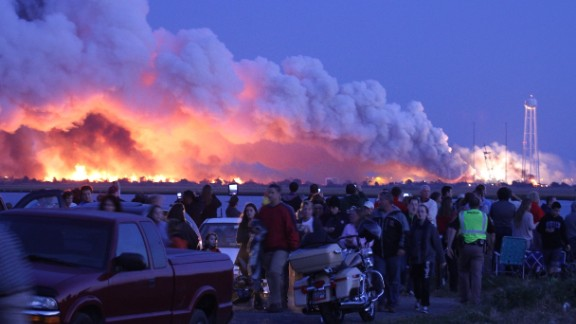 People who came to Wallops Island to watch the launch walk away after the unmanned rocket, owned by Orbital Sciences Corp., exploded.
