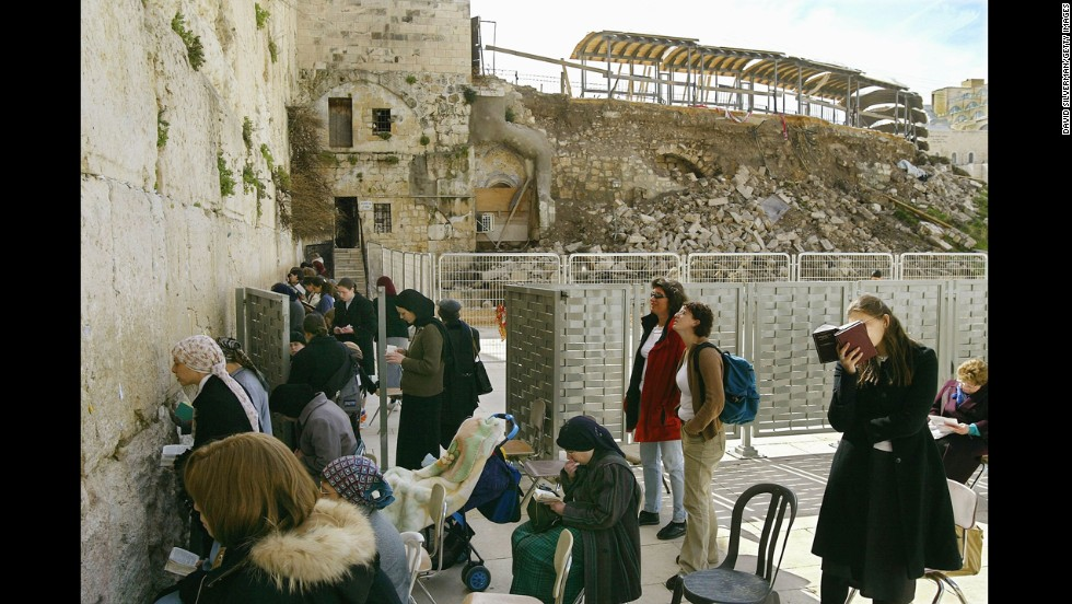 Jewish women pray behind a barrier at the Western Wall in February 2004, following a collapse of the wall into the prayer area.
