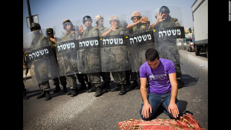 A Palestinian worshipper who was prevented from reaching the al-Aqsa Mosque prays outside Jerusalem's Old City while Israeli forces stand guard in March 2010. Police had temporarily limited access.