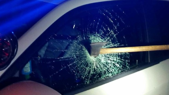 This photo provided by the Washington Metropolitan Police Department shows an ax in the window of a police car.