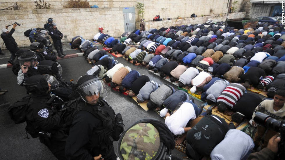 Israeli border police block a road in Jerusalem as Muslims pray Friday, October 31. A day after taking the rare step of closing the Temple Mount, Israel partially reopened access for Muslim prayers Friday. But midday access was granted only to men over 50 and women. Israeli police said this was meant to prevent demonstrations by young Muslim men following the recent shootings of a controversial rabbi and a Palestinian suspect in the rabbi's shooting.
