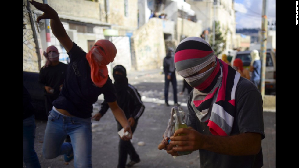 Palestinians throw stones in the streets of Jerusalem on October 30.