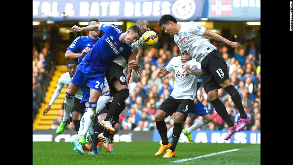 Chelsea's Gary Cahill, left, and QPR's Yun Suk-young lower their heads as they go for a ball Saturday, November 1, in London. Chelsea won the home match 2-1 to stay atop the Premier League.