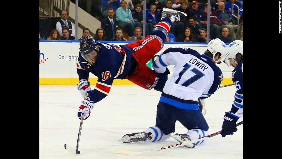 Marc Staal of the New York Rangers gets a shot off as he is flipped by Winnipeg's Adam Lowry during an NHL game played Saturday, November 1, in New York.