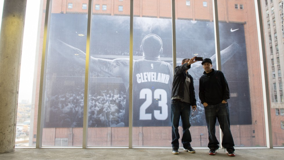 People take a photo of themselves in front of a LeBron James banner outside Cleveland's Quicken Loans Arena on Thursday, October 30. After playing several seasons in Miami, the basketball star recently returned to the NBA team that drafted him, the Cleveland Cavaliers.