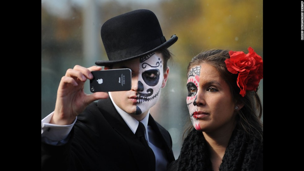Patrick Flanagan and Alicia Martinez take a selfie Sunday, November 2, during the Day of the Dead community procession around Detroit's Clark Park.