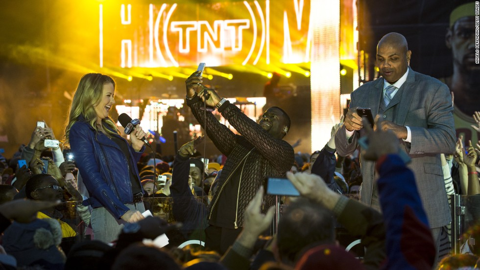 Comedian Kevin Hart, center, snaps a selfie during the Cleveland Cavaliers' Fan Fest party on Thursday, October 30. On stage with Hart are television personalities Kristen Ledlow and Charles Barkley.