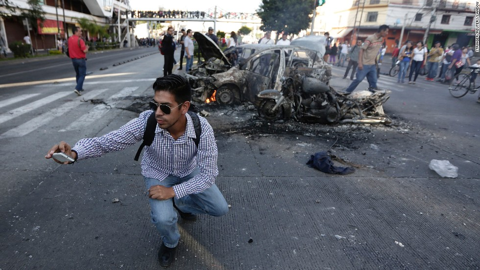 A man in Guadalajara, Mexico, takes a selfie in front of vehicles burned by street vendors and shopkeepers following a police operation to seize counterfeit products on Friday, October 31.