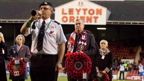 A man wears a Hearts scarf and holds a wreath to represent the Scottish club during a remembrance ceremony at Orient