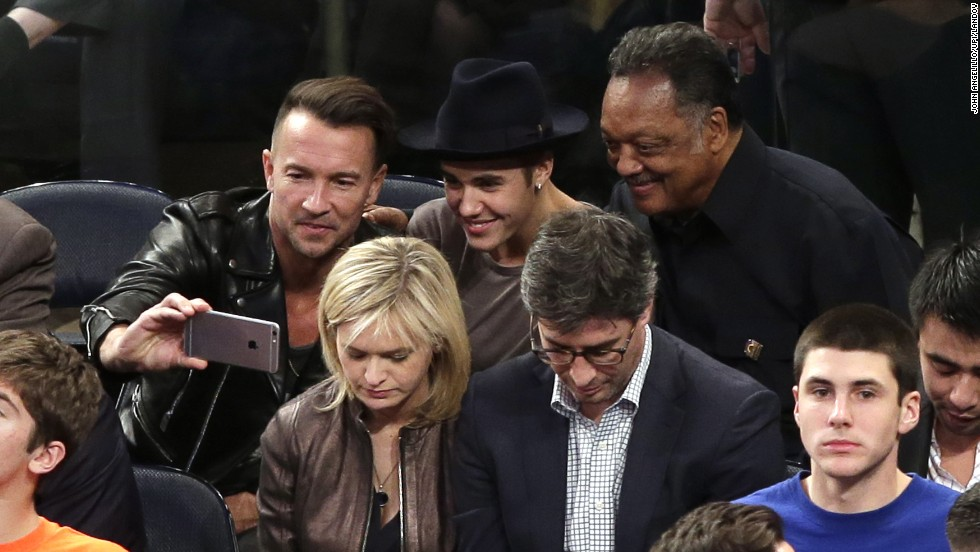 Pastor Carl Lentz snaps a selfie with pop star Justin Bieber and the Rev. Jesse Jackson at an NBA basketball game Wednesday, October 29, in New York.