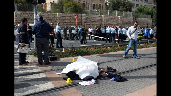 The body of a Palestinian attacker lies covered on the rails at a Jerusalem light train station on Wednesday, November 5. A police spokeswoman said the man was shot and killed after he deliberately rammed his vehicle into a crowd of pedestrians, then got out of the vehicle and attacked people with a metal bar. One pedestrian, an Israeli border police officer, was killed and 14 other people were injured.