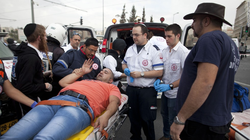 Rescue workers and paramedics carry an injured man to an ambulance.<br />Los equipos de rescate y paramédicos llevan a un hombre herido a una ambulancia.
