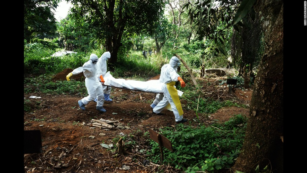 Health workers carry the body of a person who died from ebola to the cemetery.