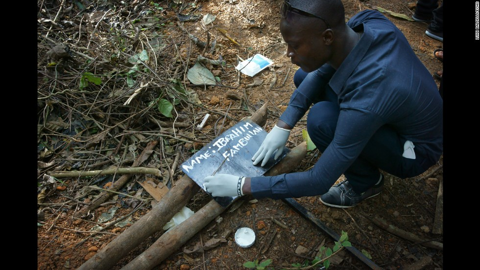 A man writes the name of another man, Ibrahim Fambullah, who died of ebola, on an iron slab in the area of the cemetery reserved for the deaths of Ebola.
