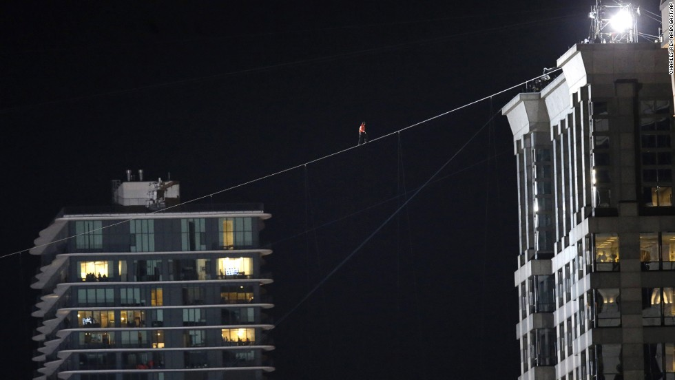 Daredevil Nik Wallenda makes his tightrope walk uphill at a 19-degree angle from the Marina City west tower across the Chicago River to the top of the Leo Burnett Building in Chicago on Sunday, November 2.