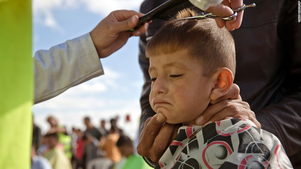 A Syrian Kurdish child from the Kobani area has his hair cut by a volunteer at a refugee camp in Suruc, near the Turkey-Syria border, on Sunday, November 2. ISIS militants have been advancing in Iraq and Syria as they seek to create an Islamic caliphate.