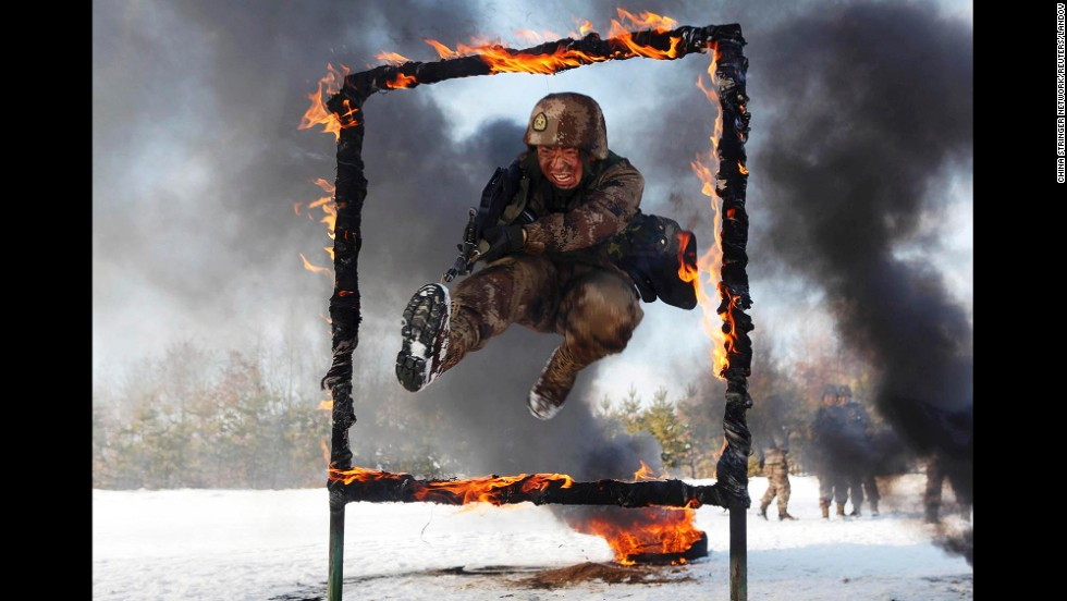 A People's Liberation Army soldier jumps through a burning obstacle during a training session in Heihe, China, near the border with Russia on Friday, October 31.