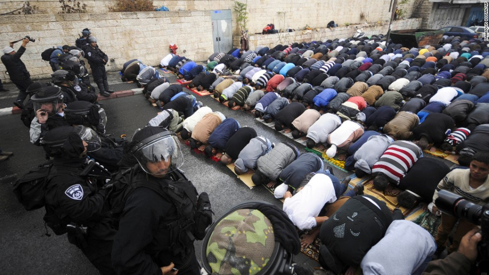 Israeli border police block a road in Jerusalem as Muslims pray Friday, October 31. A day after taking the rare step of closing the Temple Mount, Israel partially reopened access for Muslim prayers Friday. But midday access was granted only to men 50 or older and to women. Israeli police said this was meant to prevent demonstrations by young Muslim men following the recent shootings of a controversial rabbi and a Palestinian suspect in the rabbi's shooting.