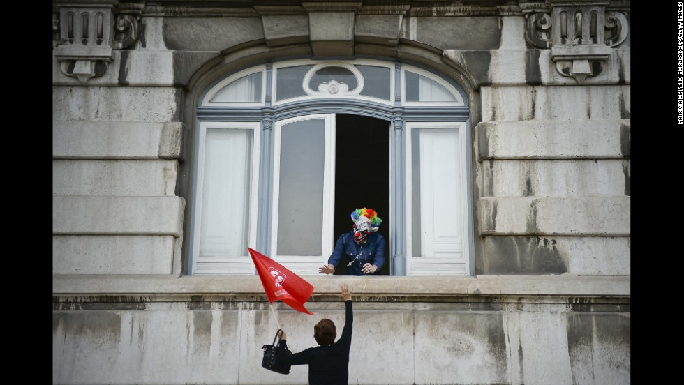 A demonstrator waves to a man dressed up as a clown during a demonstration against wage cuts and increased working hours in Lisbon, Portugal, on Friday, October 31.