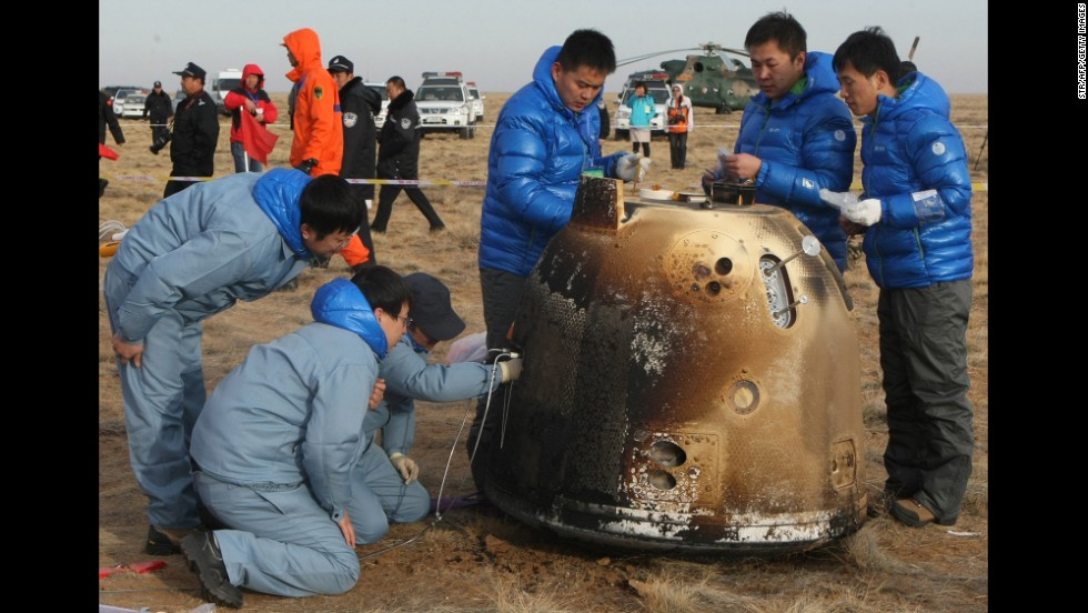 Technicians check an unmanned probe on Saturday, November 1, after it returned from its mission to the moon and landed in north China's Inner Mongolia region. The landing completes China's first return mission to the moon.