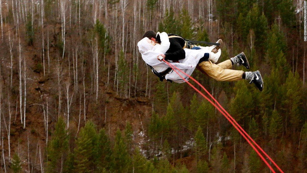 "Newly married members of the amateur rope-jumping group ""Exit Point"" jump from a 144-foot bridge in the Siberian Taiga area outside Krasnoyarsk, Russia, on Sunday, November 2."