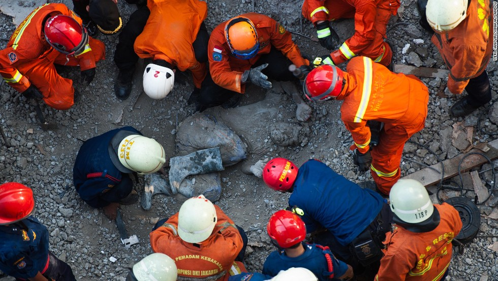Rescuers gather around a body during search operations after a building collapsed in Jakarta, Indonesia, on Friday, October 31.