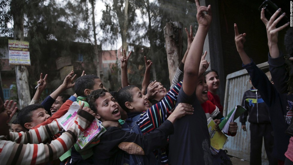 Egyptian children push each other as a woman takes a photograph of them with her phone on Wednesday, November 5, in the village of Dierb, Egypt, about 75 miles northeast of Cairo.