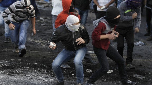 Masked Palestinian youths throw stones during clashes with Israeli security forces in the Palestinian refugee camp of Shuafat in east Jerusalem, on November 7, 2014