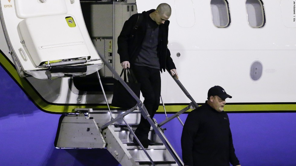 Matthew Miller, top, walks off the plane after arriving back in the United States.