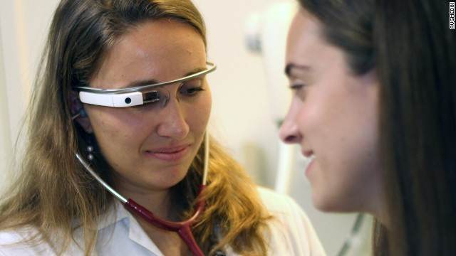 A doctor wearing Google Glass treats a patient. Google is working with companies on bringing the wearable into workplaces to improve productivity.