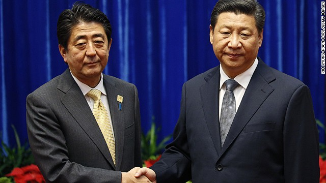 China's President Xi Jinping, right, shakes hands with Japan's Prime Minister Shinzo Abe.
