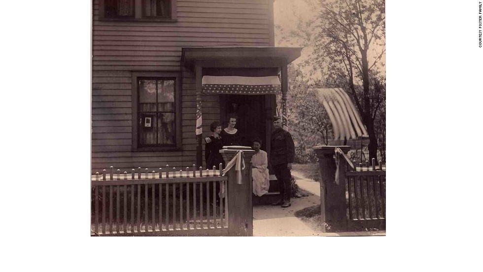 Back home in 1919, Foster joins his mother and two sisters outside their La Crosse, Wisconsin, house, which was draped in red, white and blue decorations.