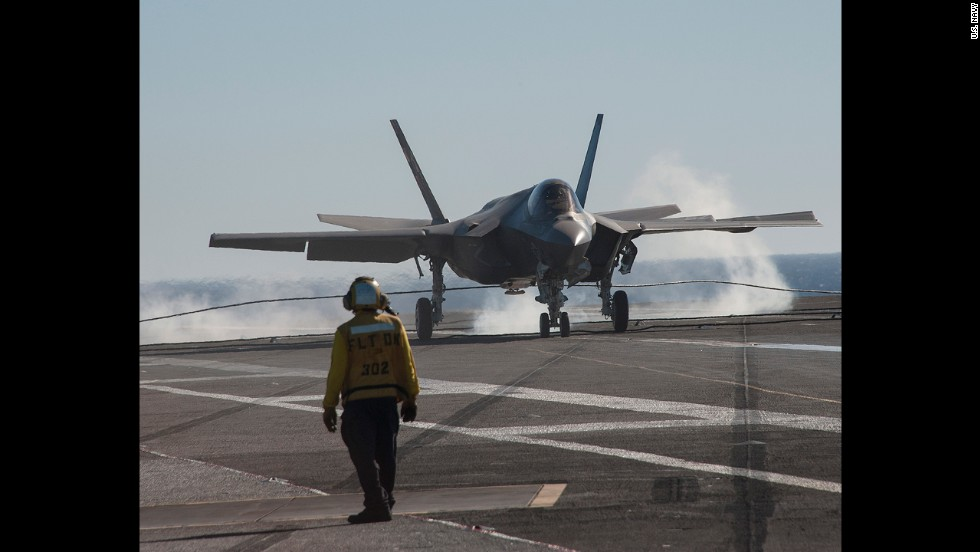 An F-35C jet lands on the deck of the USS Nimitz. To stop, the jet uses a tailhook to grab a wire stretched across the aircraft carrier's deck.