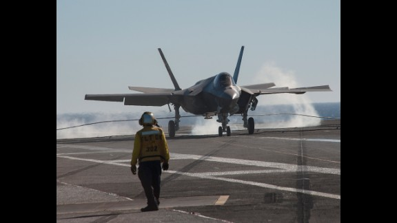 An F-35C jet lands on the deck of the USS Nimitz. To stop, the jet uses a tailhook to grab a wire stretched across the aircraft carrier