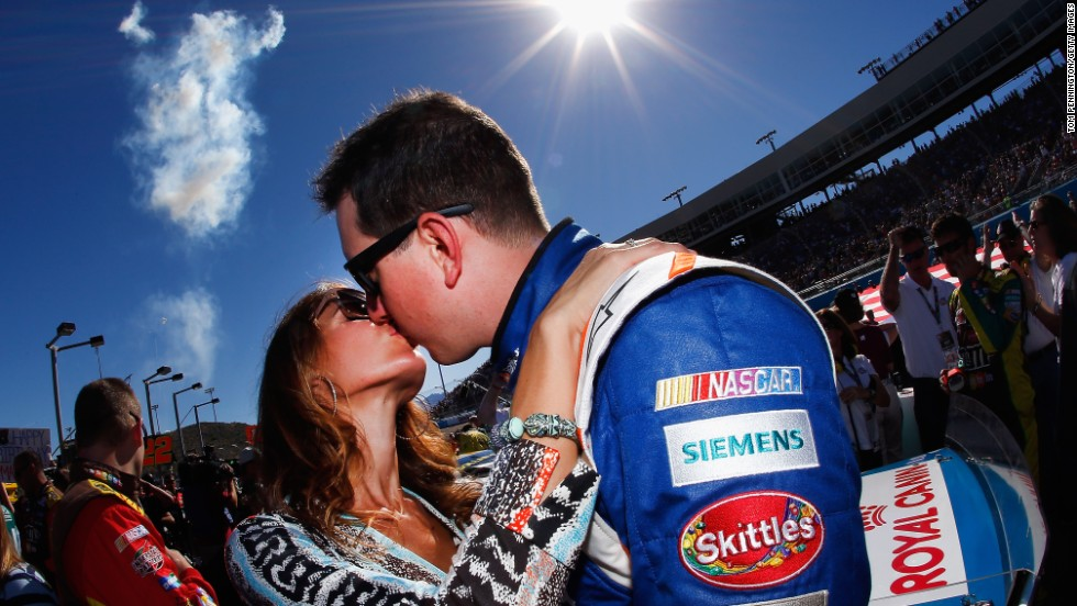 Kyle Busch kisses his wife, Samantha, prior to the start of the NASCAR Sprint Cup Series Quicken Loans Race for Heroes 500 at the Phoenix International Raceway in Avondale, Arizona, on Sunday, November 9.