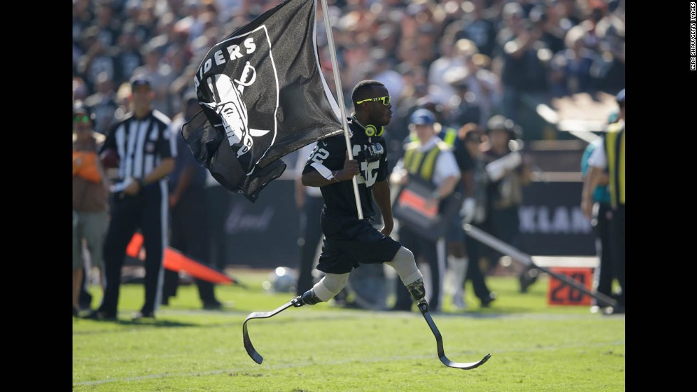 Olympic sprinter Blake Leeper carries an Oakland Raiders flag during the team's game against the Denver Broncos on Sunday, November 9, at O.co Coliseum in Oakland, California. The Broncos won 41-17.