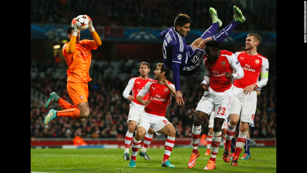 Arsenal's Danny Welbeck, second from right, challenges Anderlecht's Cyriac as Arsenal's goalkeeper Wojciech Szczesny catches the ball during their Champions League match at the Emirates stadium in London on Tuesday, November 4. The game ended 3-3.