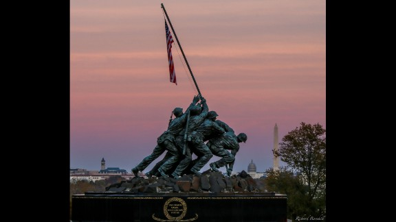 "As the sun set around Washington, D.C., Richard Barnhill caught this shot of the Marine Corps War Memorial against the pink fall sky. The Marine Corps War Memorial inscription reads: ""In honor and in memory of the men of the United States Marine Corps who have given their lives to their country since November 10, 1775."""